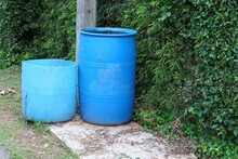 Two Large Blue Plastic Trash Cans Are Located On An Outdoor Pavement Area For Littering.
