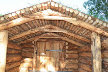 Dugout (or Dugout, Pit, Earthen House, Dug Cellar) From Logs In The Forest. A Traditional Shelter For People And Livestock Based On A Pit In The Ground.