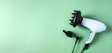 Modern Hairdryer With Diffuser On Green Large Background  For Banner. Hair Care And Styling Concept. Copy Space