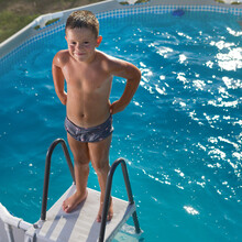 Little Boy Came Out Of The Pool, Stands Wet On The Top Step Of The Stairs