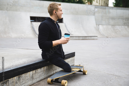 Foto Handicapped guy with a cup of coffee before longboard riding in a skatepark