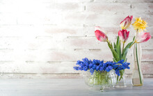Flowers Of Tulips, Grape Hyacinths, And Daffodil In A Jar And Crystal Glass On A Rustical Brick Wall With Copy Space