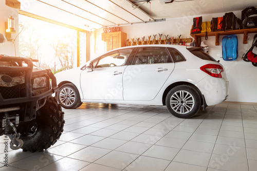 Canvas Print Home suburban countryside modern car and ATV double garage interior with wooden shelf, tools and equipment stuff storage warehouse indoors against sun light
