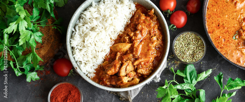 Traditional curry and ingredients. Tikka Masala chicken and rice. Indian food. Top view. Copy space. Dark background.