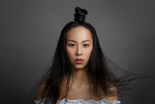 Portrait Of A Beautiful Asian Girl With A Puss Hairstyle And Hair Fluttering In The Wind Isolated On A Dark Background.