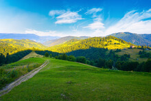 Rural Landscape In Mountains At Summer Sunrise. Country Road Through Grassy Pasture Winding Down In To The Distant Valley. Clouds On The Blue Sky Above The Ridge In The Distance