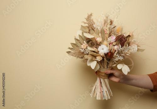 Woman holding beautiful dried flower bouquet on beige background, closeup Fototapet