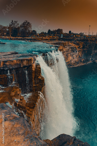 Picturesque landscape of a waterfall flowing into the blue waters of a river Wall mural