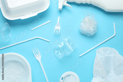 Different plastic items on light blue background, flat lay