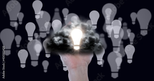 Composition of lit light bulb with cloud over hand and multiple light bulbs on black background