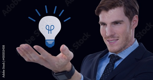 Composition of lit light bulb icon over businessman's hand on black background