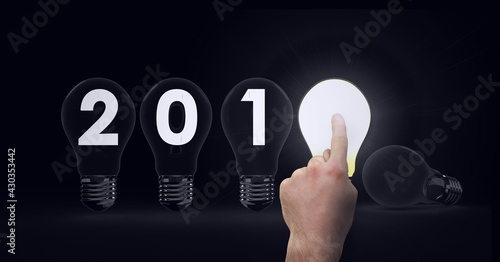 Composition of 201 written on light bulbs with finger touching lit light bulb on black background