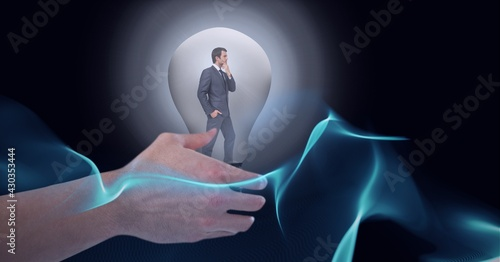 Composition of hand over businessman thinking inside light bulb over halo on black background