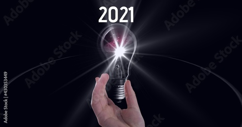 Composition of 2021 with hand holding lit light bulb on black background