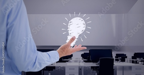 Composition of lit light bulb icon over businessman's hand in empty office
