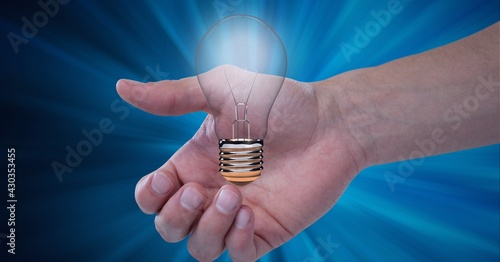 Composition of lit light bulb over man's hand on blue background