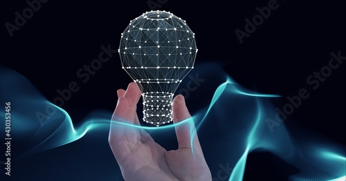 Composition of hand holding light bulb with network of connections and blue light trails