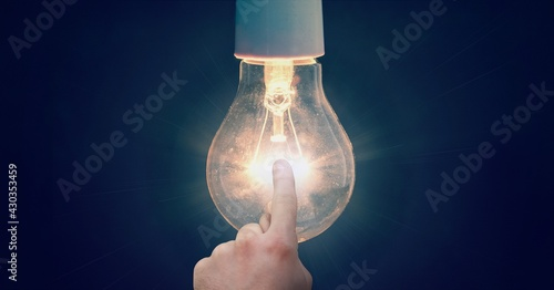 Composition of finger touching lit light bulb on blue background