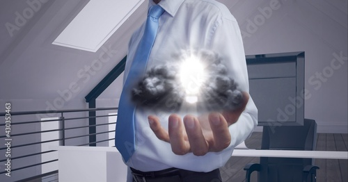 Composition of lit light bulb with clouds over businessman's hand in office