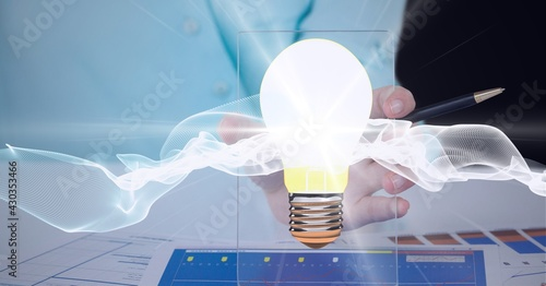 Composition of lit light bulb over man's hand with white light trails