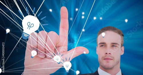 Composition of man touching virtual screen with light bulb icons with network of connections