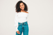 Beautiful Black Woman With Afro Curls Hairstyle.Smiling Model In Sweater And Trendy Jeans Clothes. Sexy Carefree Female Posing On White Background In Studio. Tanned And Cheerful