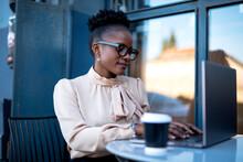 Businesswoman Drinking Coffee In Cafe. Beautiful Woman Working On Laptop In Coffee Shop.