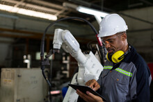 African American Male Engineer Worker Using Tablet With The Automatic Robotic Machine In The Factory. Black Male Technician Worker Working With Control Automatic Robot Arm System Welding