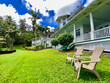 Beautiful romantic colonial architecture guest house bed and breakfast hotel resort with breathtaking tropical garden eden paradise outlook view over Ocean with lush vegetation on Hawaiian Big Island
