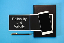A White Notebook With Black Pages, A Smartphone And A Pen On A Blue Background. The Inscription Reliability And Validity