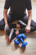 Fit,sport.Home fitness,remote training online with virtual instructor.Woman in sportswear sitting floor with dumbbells home. Sports and recreation concept lockdown with fitness apps online.Home fit