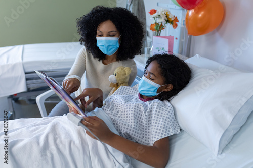 Mixed race mother and sick daughter in face masks in hospital, reading book with teddy bear