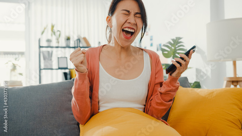 Photo Beautiful asian lady sit on sofa feel exciting with great news at home
