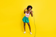 Full Size Photo Of Pretty Afro American Charming Woman Wear Pink Singlet Good Singer Karaoke Isolated On Yellow Color Background