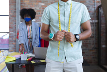 Midsection Of Mixed Race Designer Wearing Tailor's Meter, African American Female In Background