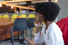 African American Woman Sitting On Pouf, Using Tablet In Cafe