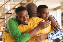 African American Senior Man And His Two Sons Hugging Each Other At Home