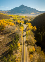Aerial View Of An Endless Road Driving Along Coal Creek With Crested Butte Mountain In Background, Crested Butte, Colorado, United States Of America.