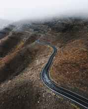 Aerial View Of An Empty Road Driving Along A Volcanic Hillside Near Mogan, Canary Islands, Spain.