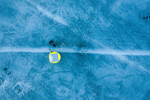 Aerial View Of A Person Staying In A Technical Yellow Winter Tent Over The Frozen River Estuary In Kauno Mariu National Park Near Kaunas, Lithuania.