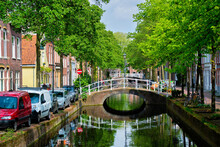 Cars On Canal Embankment In Street Of Delft. Delft, Netherlands