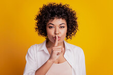 Woman With Sign Silence Forefinger Hide Lips Cunning Face Posing On Yellow Background