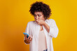 Close up portrait of shocked african american woman hold telephone close mouth