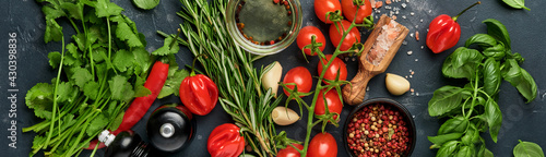 Fototapeta Food cooking background. Fresh rosemary, cilantro, basil, cherry tomatoes, peppers and olive oil, spices herbs and vegetables at black slate table. Bannr top view. obraz