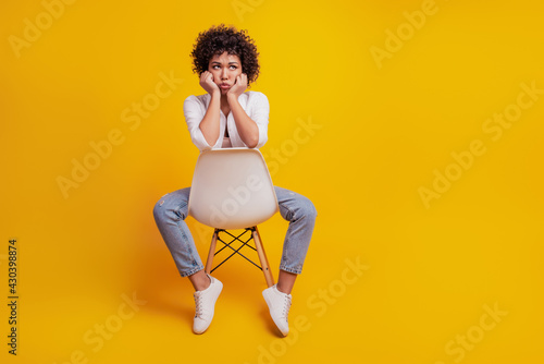 Portrait of frustrated woman crying sit chair bad mood on yellow wall Wallpaper Mural