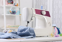 Modern Sewing Machine, Fabric And Accessories On Table Indoors