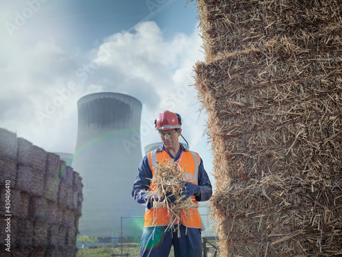 UK, North Yorkshire, Engineer at haystack in front of power station Fototapet