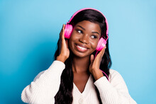 Photo Of Attractive Afro American Young Lady Look Empty Space Dream Wear Headphones Isolated On Blue Color Background
