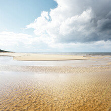 Crystal Clear Water And Sandy Shore Of The Baltic Sea On A Sunny Spring Day. Shallow Water. Dramatic Cloudscape. Latvia