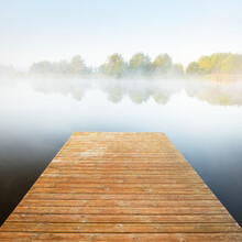 Lake Shore In A Fog At Sunrise. Wooden Pier Close-up. Forest In The Background. Symmetry Reflections In The Water. Idyllic Rural Scene. Atmospheric Landscape. Ecological Resort, Fishing, Swimming